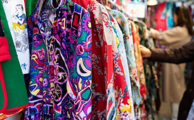 Roupa tradicional na cremalheira da roupa - armário colorido brilhante.