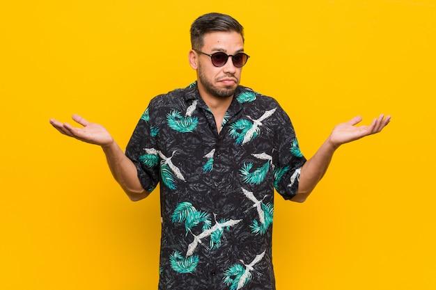 Roupa vestindo do verão do homem filipino novo que duvida e que shrugging ombros no gesto de questão.