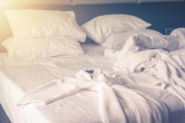 Roupão de banho na cama no quarto confortável depois de acordar com lençóis de cama bagunçado e edredon com rugas bagunçado no quarto