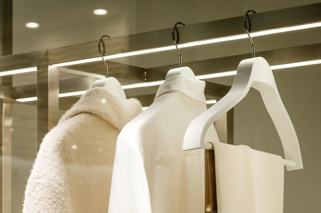 Roupas brancas penduradas em cabides brancos close-up