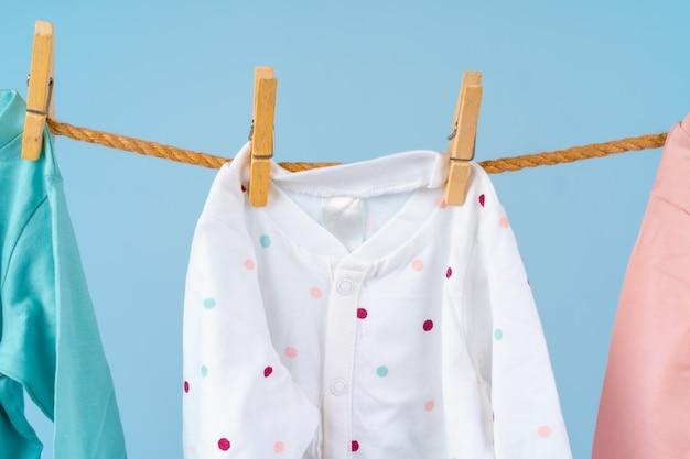 Roupas coloridas de criança fofa pendurar em uma corda