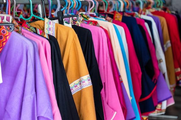 Roupas coloridas de tecido de algodão pendurado no trilho na loja