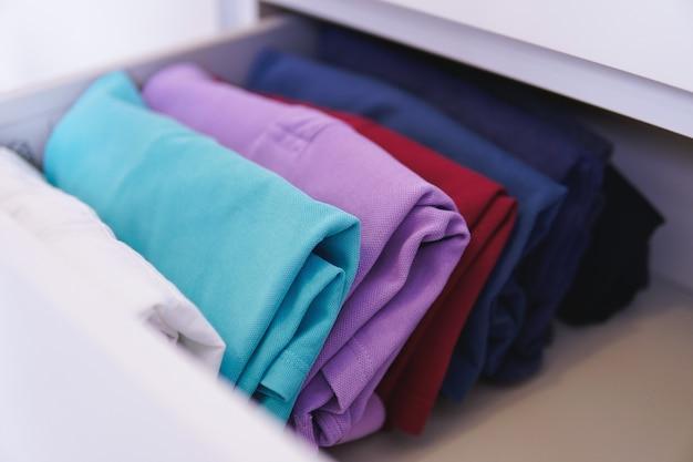 Roupas coloridas dobradas dispostas em um armário sob as luzes