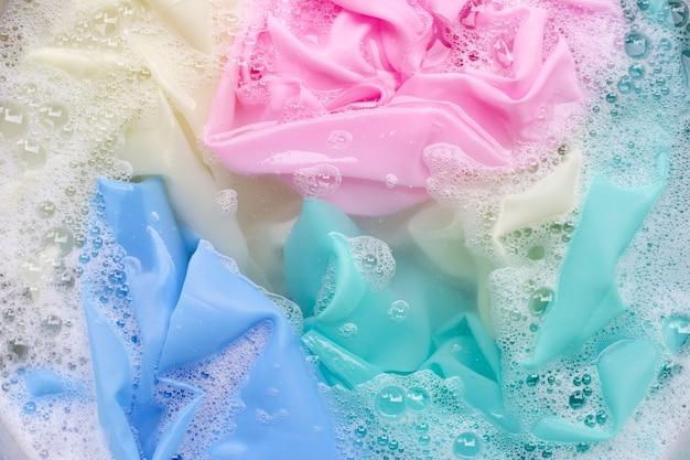 Roupas coloridas embebidas em detergente em pó dissolvido em água. conceito de lavanderia