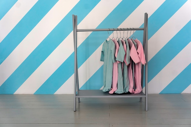 Roupas coloridas infantis penduradas em um cabide em uma loja, copie o espaço