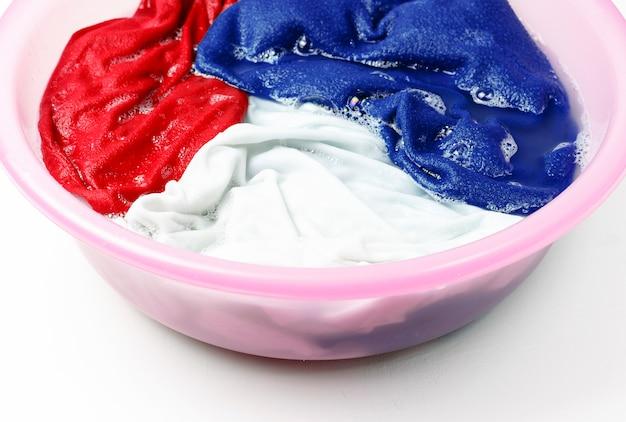 Roupas coloridas lavadas com uma bacia com bolhas de sabão