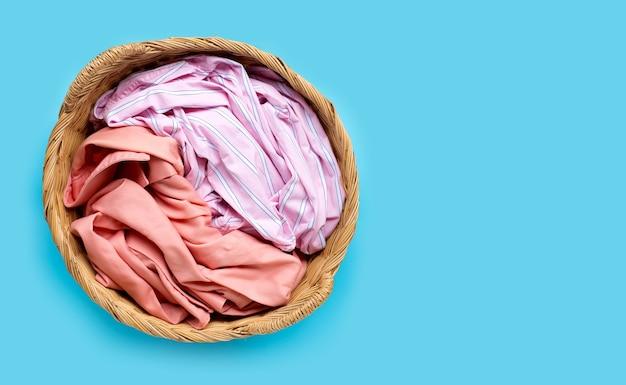 Roupas coloridas no cesto de roupa suja sobre fundo azul. copie o espaço