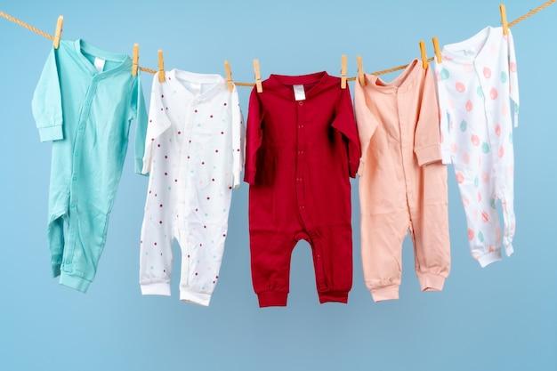 Roupas coloridas para bebês penduradas em uma corda