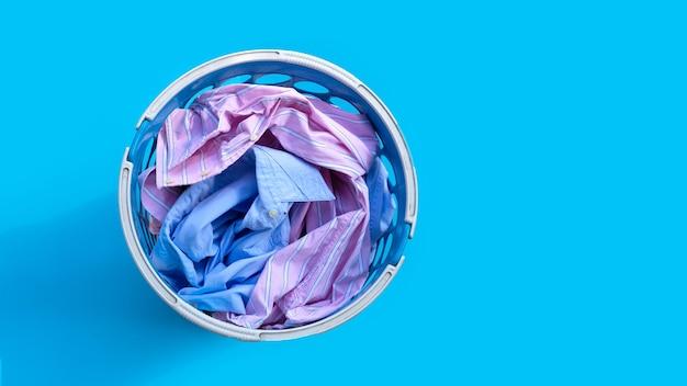 Roupas com um cesto de roupa suja em azul.