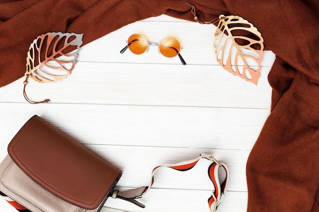 Roupas confortáveis de outono para mulher, lenço de lã e uma pequena bolsa com folhas decorativas na superfície de madeira branca.