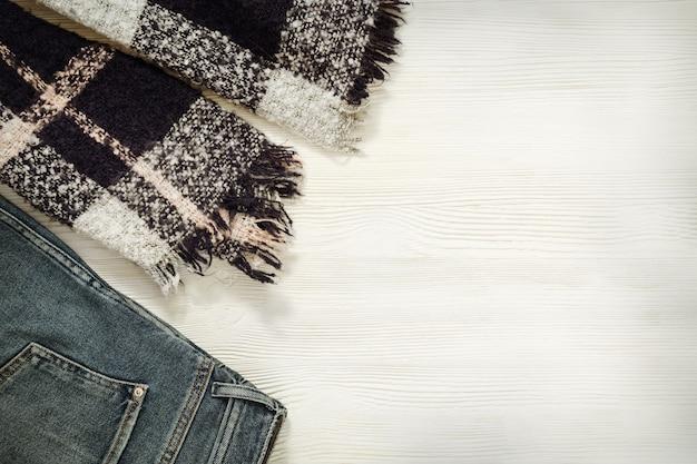 Roupas confortaveis. lenço aconchegante, jeans azul em branco de madeira.