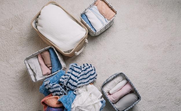 Roupas cuidadosamente dobradas em caixas organizadoras abertas, vista de cima. método de limpeza