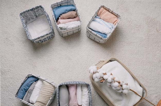 Roupas cuidadosamente dobradas em caixas organizadoras abertas, vista de cima. um ramo de algodão. o conceito de limpeza