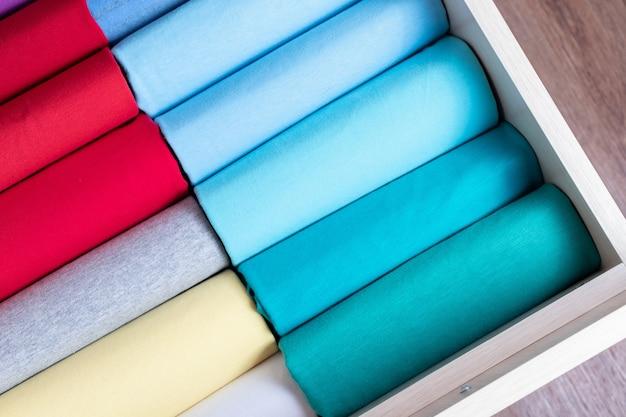 Roupas cuidadosamente dobradas na cômoda. arrumação vertical de roupas.