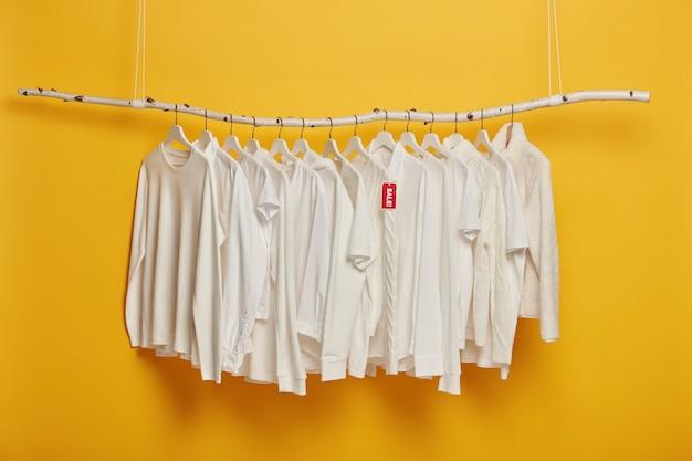 Roupas da moda brancas em cabides com venda inscrita de marca vermelha, pendurado na prateleira de madeira contra um fundo amarelo, copie o espaço.