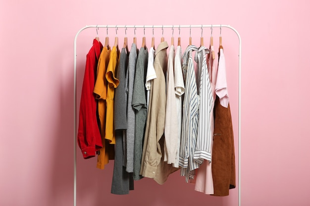 Roupas da moda em cabides em uma arara de guarda-roupa em um fundo colorido