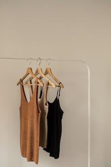 Roupas da moda feminina em tons pastel brilhantes em cabideiro em branco