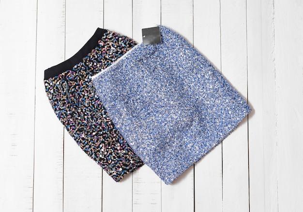 Roupas da moda. mini-saias de brilho preto e azul em pranchas de madeira branca