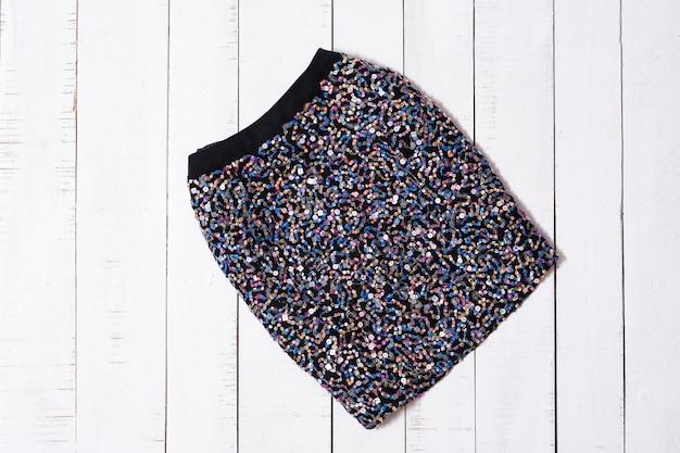Roupas da moda. mini saias de brilho preto em pranchas de madeira branca