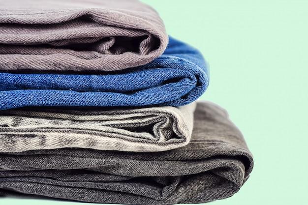 Roupas da moda, pilha de jeans no fundo.