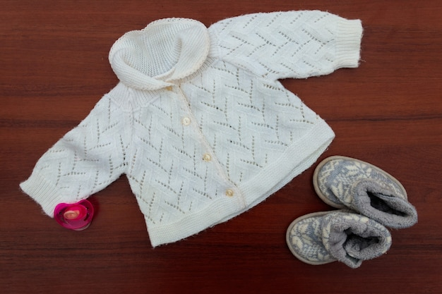 Roupas de bebê, botinhas e chupeta em fundo de madeira. kit para recém-nascidos