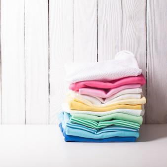 Roupas de bebê coloridas com pilha dobrada em um fundo branco