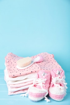 Roupas de bebê com botinhas e pente em fundo azul