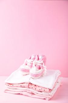 Roupas de bebê com botinhas em fundo rosa com espaço de cópia