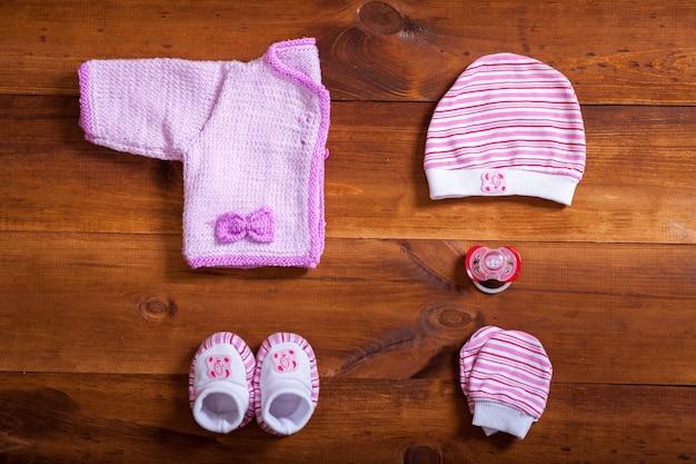 Roupas de bebê e acessórios na mesa de fundo de madeira marrom, plana leigos