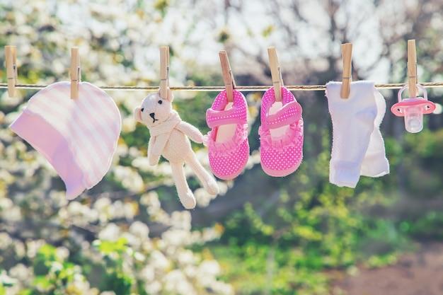 Roupas de bebê e acessórios pesam na corda depois de lavar ao ar livre. foco seletivo.