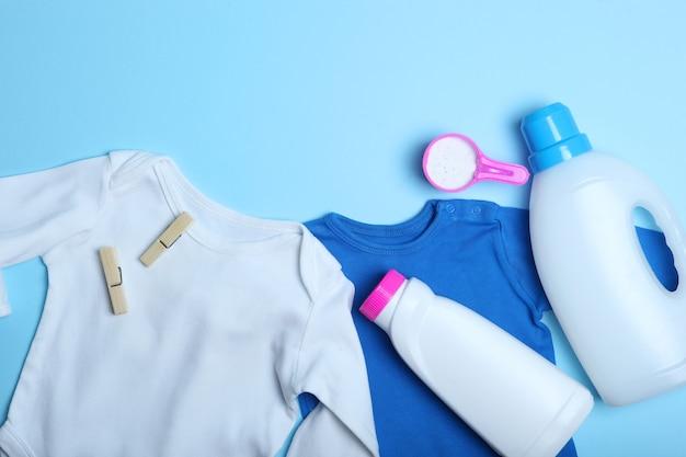 Roupas de bebê e detergentes em uma vista superior de fundo colorido