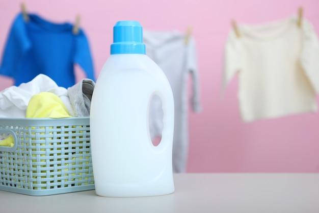 Roupas de bebê e detergentes na mesa conceito de cuidados com roupas de bebê