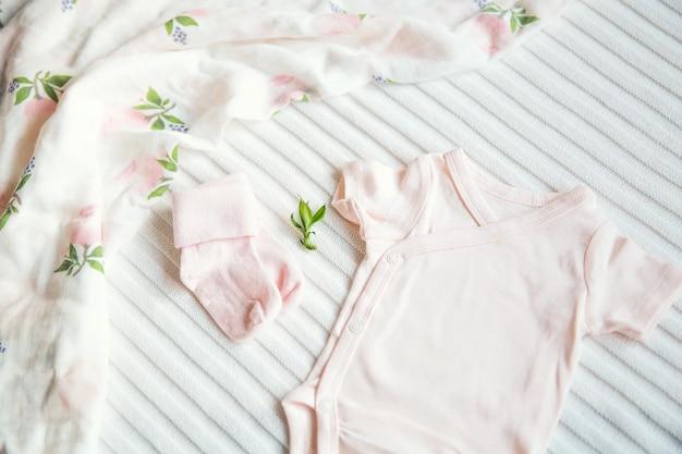 Roupas de bebê e necessidades em fundo de tecido claro suave, suave e aconchegante