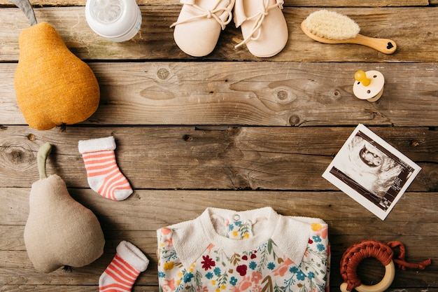 Roupas de bebê e produtos dispostos em forma circular na mesa de madeira
