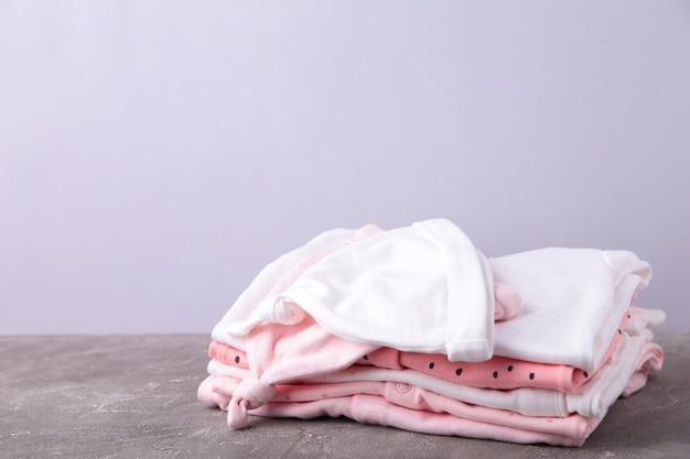 Roupas de bebê em fundo cinza
