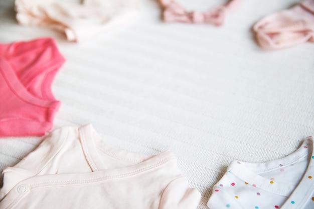 Roupas de bebê em fundo de tecido pastel claro ambiente suave, suave e aconchegante