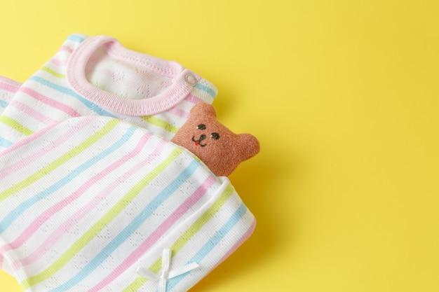 Roupas de bebê em uma superfície amarela