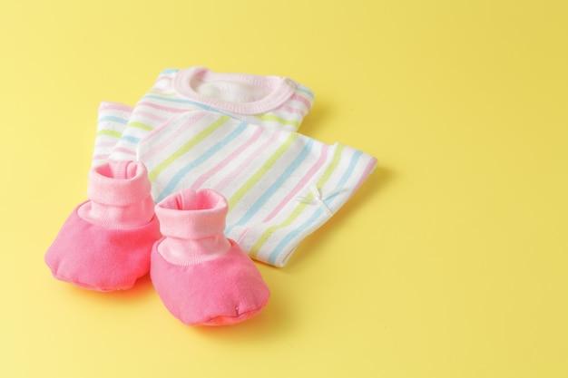 Roupas de bebê em uma superfície plana e brilhante