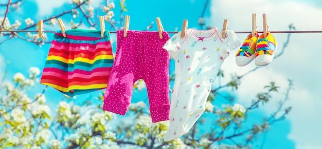 Roupas de bebê estão secando na rua