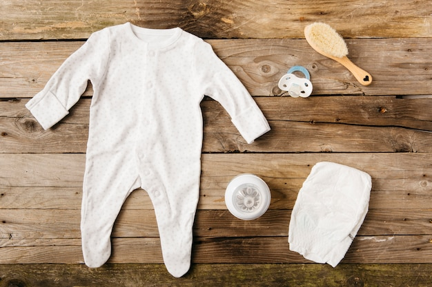 Roupas de bebê; garrafa de leite; chupeta; escova e fralda na mesa de madeira
