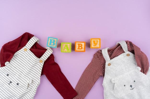 Roupas de bebê menina em fundo pastel lilás
