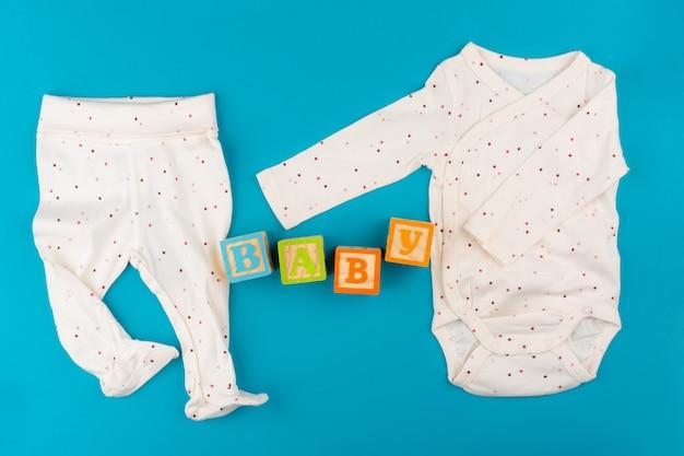 Roupas de bebê na superfície azul vista superior