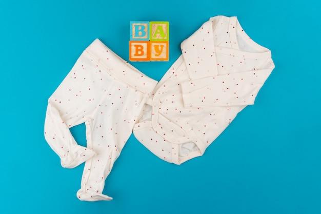 Roupas de bebê na vista superior azul