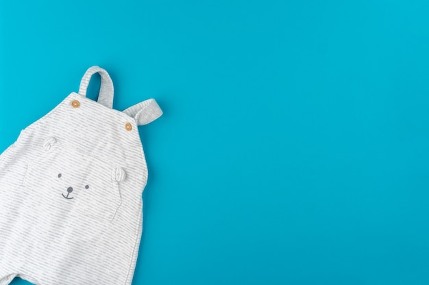 Roupas de bebê na vista superior do fundo azul