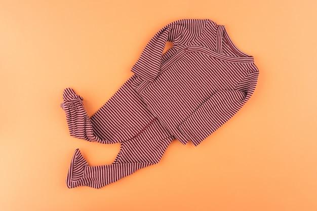 Roupas de bebê na vista superior do plano de fundo laranja