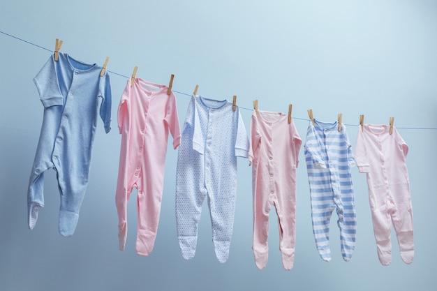 Roupas de bebê penduradas em uma corda em fundo cinza