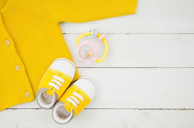 Roupas de bebê plana leigos com fundo de madeira