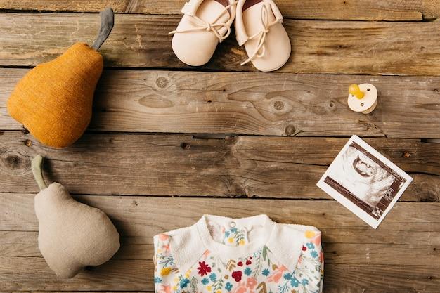 Roupas de bebê; sapatos; chupeta; imagens de ultra-som e pêra recheada na mesa de madeira