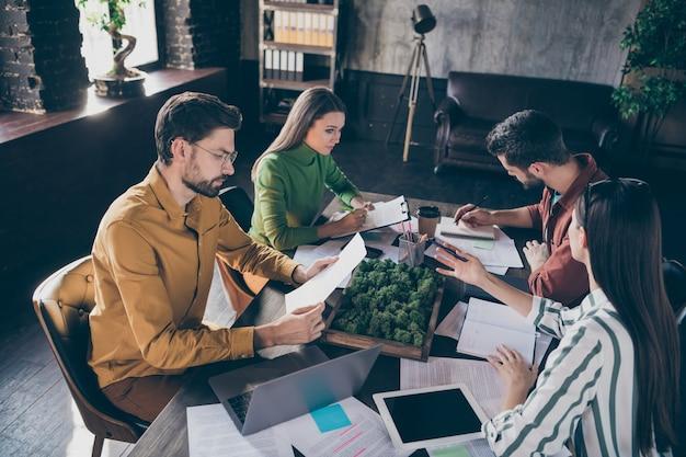 Roupas de estilo casual vestindo pessoas ceo colares sentar mesa mesa analisar relatório de progresso de desenvolvimento de treinamento inicial