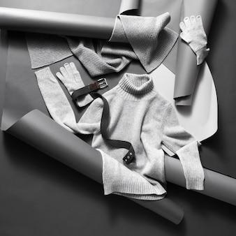 Roupas de inverno. conjunto de lindas roupas leves unissex em papel cinza e parede preta